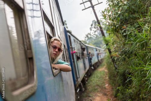 Poster Blonde caucasian woman looking trough old retro blue train window , traveling by train in third world country