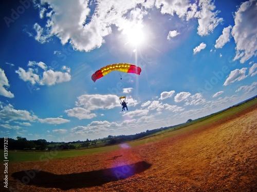 Zdjęcia na płótnie, fototapety, obrazy : Parachute tandem landing with lens flare