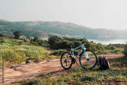 Poster Bicycle with backpack on hill top, scenic view behind them