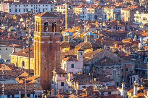 Aerial view of Venice, Italy, at sunset with rooftops of building, the sea and warm sunlight. © Augustin Lazaroiu