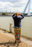 Man with bicycle photographing the Erasmus Bridge in Rotterdam