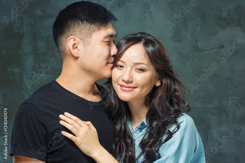 Portrait of smiling Korean couple on a gray