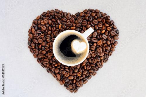 antecedentes-del-cafe-dia-de-san-valentin-granos-de-cafe-en-forma-de-corazon-y-una-taza-de-cafe-recien-hecho