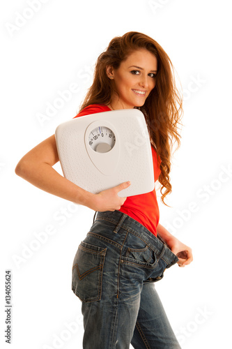 Beautiful young woman holding scale and too big trousers as she