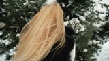 Blonde woman in a snow tree rejoices revolves around and sends kisses. She thanks for the gift, jumps for joy, many times ready to kiss. Her dearest wish fulfilled, the model enjoys and admires. The
