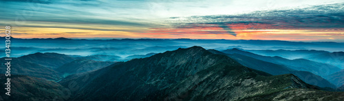 Foto op Canvas Panoramafoto s Panorama with blue mountains and hills at sunset