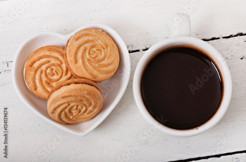 Poster Cup of coffee and delicious baked cookies on old wooden background
