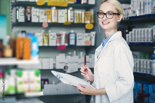 Tuinposter Apotheek woman pharmacist is holding a notepad