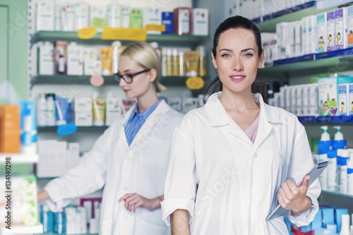 Papiers peints Pharmacie young woman pharmacist is holding a tablet pc