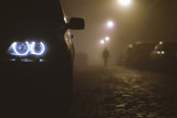 The car headlight with a walking man on the background of a fog