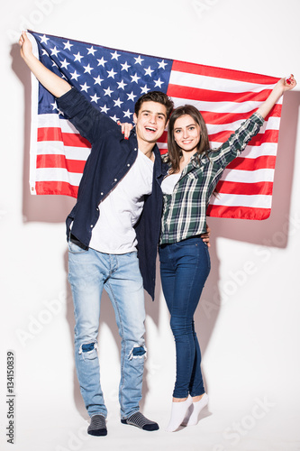 Poster Portrait of a young happy couple on the background of the US flag