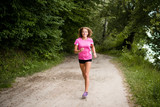 Healthy and happy woman jogging in urban park