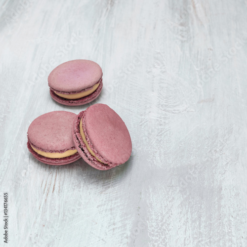Foto op Canvas Macarons Pink macarons on pale whitewashed board with copyspace