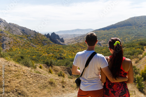 Poster Couple hugging against mountain landscape