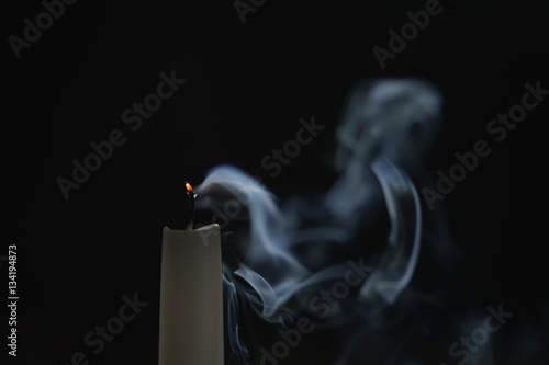 Poster tall candle with smoke trail in the dark environment, shallow focus