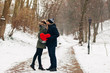 Young couple man and woman hug and kiss in Park at winter and holding red big heart in hands