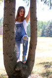Woman in overalls stands between tree trunks