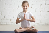 Portrait of smiling girl child on yoga meditation session, sitting in Padmasana exercise, Lotus pose with Namaste, working out wearing sportswear, indoor full length, white loft studio background