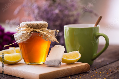 Poster fresh cup of tea with honey and lemon background.