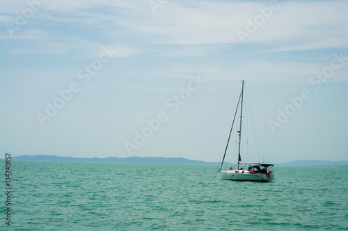 A sailboat is waiting in day stillness under beautiful blue sky with clouds on Lake Balaton, Hungary Poster