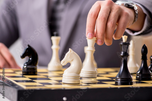 Poster Young businessman playing chess in the office