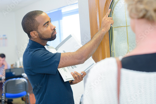 Poster Salesman showing display door to customer