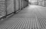 Fototapety Metal footbridge, metallic walkway and corridor, steel bridge, perspective and vanishing point,  grey atmosphere with nobody