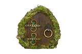Fairy door with moss on isolated background/Fairy door with moss, wood, brass ornaments and jewels