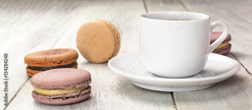 Foto op Canvas Macarons Cup of coffee with pastel colored macarons and copyspace