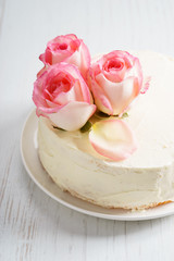 sweet white buttercream cake with pink rose flowers on top