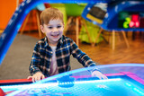 Boy playing air hockey at indoor playground