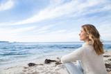 femme en hiver assise au bord de la mer - 134326279