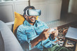 Bearded african man enjoying virtual reality glasses while relaxing on sofa.Happy young guy with vr headset or 3d spectacles and controller gamepad playing video game at home.Blurred background.