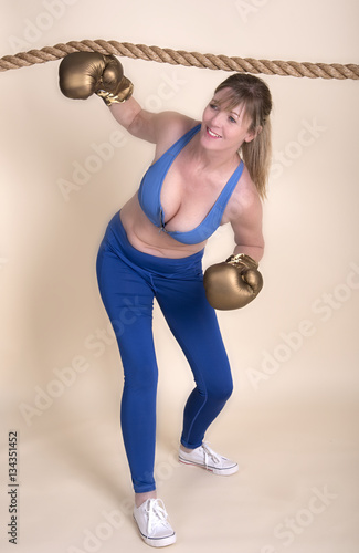 Poster Woman boxer wearing golden gloves and a sports bra ducking under a rope