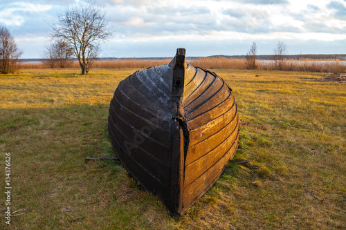Poster Upturned old fisher wooden boat lying near the lake in the grass