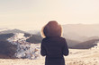 Winter view of a young woman admiring mountain landscape. Selective focus. Film filter