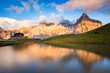 Quadro The Pale di San Martino peaks (Italian Dolomites) reflected in the water at sunset, with an alpine chalet on background.