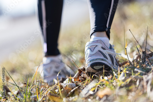 Poster feet of a running woman outdoors