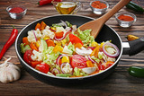 Fresh vegetables in pan and wooden spatula on table closeup