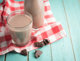Glass of chocolate milk on vintage wood background