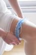 Leinwanddruck Bild - Braut zieht sich Strumpfband an