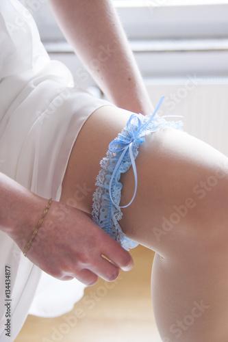 Leinwanddruck Bild Braut zieht sich Strumpfband an
