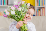 kleiner junge mit tulpenstrauß zum muttertag