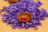 Close-up of a bowl with saffron pistils on a pile of roses saffron - 134445827