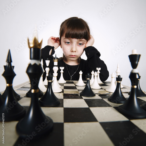 Poster little girl playing chess on white