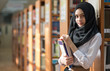 Muslim girl student in the library. She standing and holding a book.