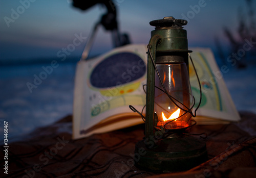 Poster Burning oil lamp standing on a map of the sky in the winter on a background of s