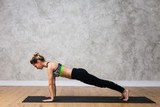 Young woman practicing Plank, Dandasana yoga pose against texturized wall / urban background