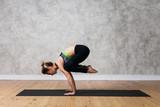 Young woman practicing yoga Crane pose, Bakasana against texturized wall / urban background
