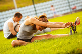 Young woman with her friends exercising on sport field.They sitting on grass and stretching.